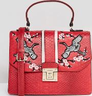 embroidered top handle bag with cross body strap