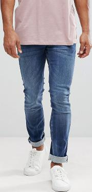 straight fit jeans in dark wash blue with distressing
