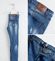 muscle fit jeans in blue with distressing