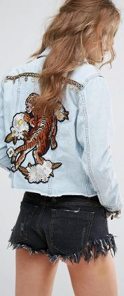customised denim trucker jacket with tiger and coin embellishment