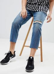 tapered jeans in midwash blue with knee rip