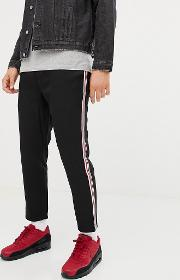 trousers in black with red and white side stripe