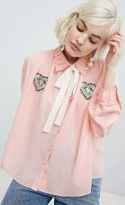 blouse with ribbon tie and heart patch detail